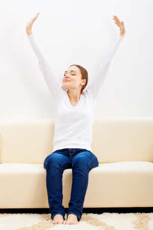 happy woman sitting on sofa and rising up hands Stock Photo - 17606698