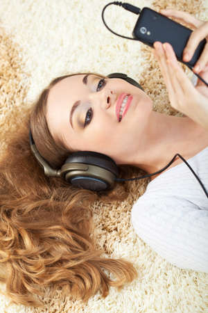 brunette woman lying on carpet and listening to music Stock Photo - 17606765