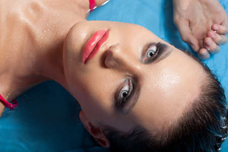 make up model: closeup brunette woman face wearing pink bra with smoky eyes laying in water