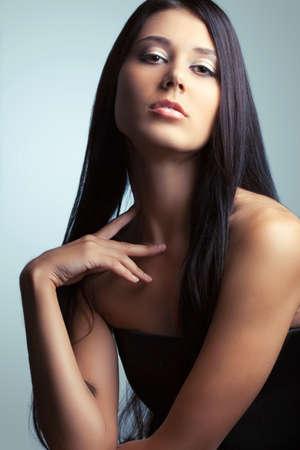 pelo castaño claro: hermosa mujer morena holdnig dedos en el cuello Foto de archivo