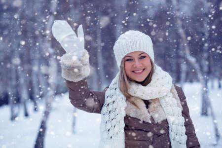 blonde woman waving in winter park during snowfall