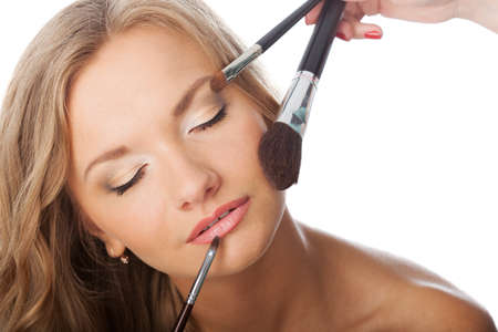 blonde woman with cosmetic brushes on her face photo