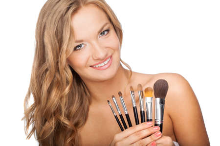 happy blonde woman holding set of cosmetic brushes photo