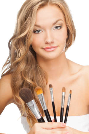 beautiful blonde woman holding set of cosmetic brushes photo