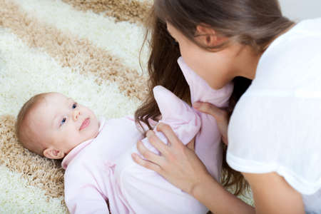 young mother playing with her baby on carpet at home photo