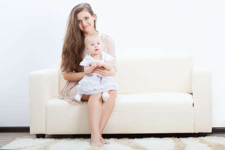 happy beautiful young mother and baby on sofa photo