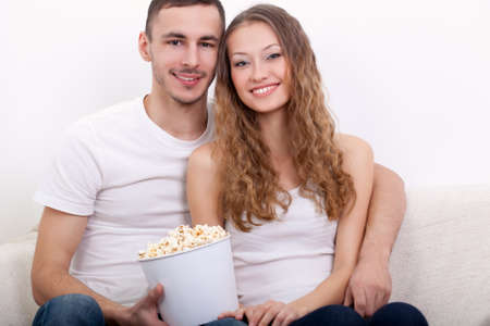 happy young couple sitting on the sofa eating popcorn and watching  tv photo