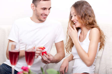 young man giving ring for his girlfriend at home interior, they laughing photo