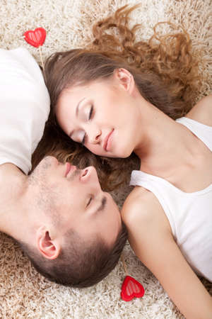 young happy couple lying on the carpet with closed eyes photo