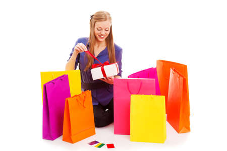 woman sitting on the floor behind shopping bags and opening gift box, isolated over white photo