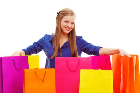 happy blonde woman sitting on the floor behind shopping bags , isolated over white photo