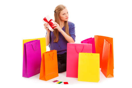 woman sitting on the floor behind shopping bags and holding gift box  Isolated over white photo