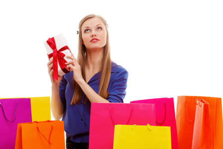 woman sitting on the floor behind shopping bags and holding gift box, isolated over white photo