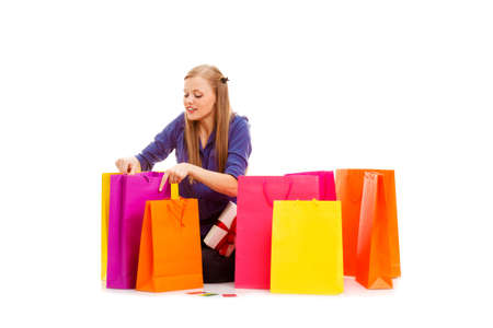 happy woman sitting on the floor behind shopping bags and opening ones photo