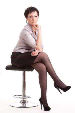 seriously: portrait of adult businesswoman sitting on chair over white background Stock Photo