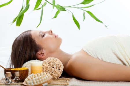 beautiful woman in a spa getting procedures under branch of bamboo photo