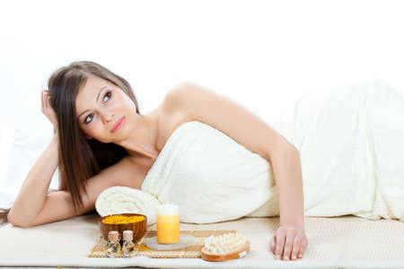 happy beautiful woman wearing towel dreaming  in spa salon photo