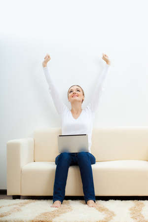 happy   woman sitting on sofa with laptop and rising hands up Stock Photo - 17788141