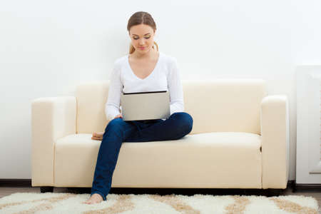 happy brunette  woman sitting on sofa with laptop Stock Photo - 17788134