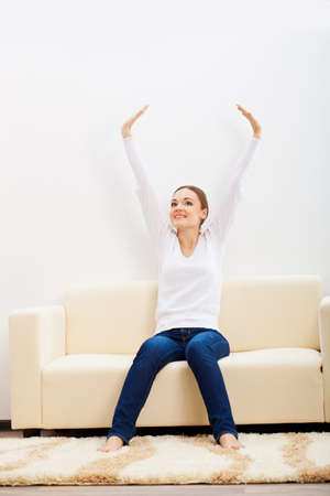 happy brunette woman sitting on sofa and rising up hands Stock Photo - 17788169