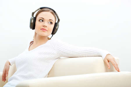 brunette woman on the sofa listening to music with closed eyes Stock Photo - 17788121
