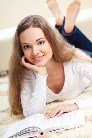 smiling woman lying on carpet with book and looking at camera Stock Photo - 18200947