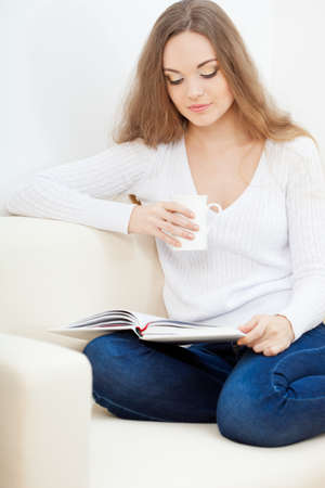 woman sitting on the sofa with white cup and reading the book Stock Photo - 18200963