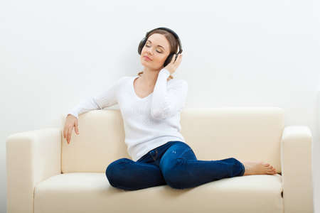 woman relaxing: brunette woman on the sofa listening to music with closed eyes Stock Photo