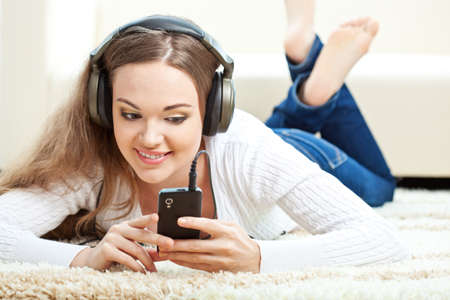 attractive gorgeous: brunette woman lying on carpet and listening to music Stock Photo