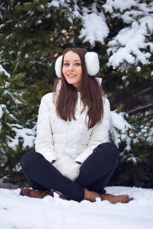 brunette woman sitting  in winter park under fur tree photo