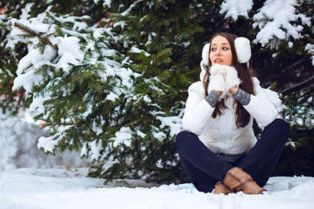 beautiful brunette woman sitting  in winter park under fur tree photo