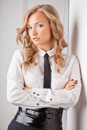 sexy teacher: closeup seriously blonde businesswoman portrait near wall