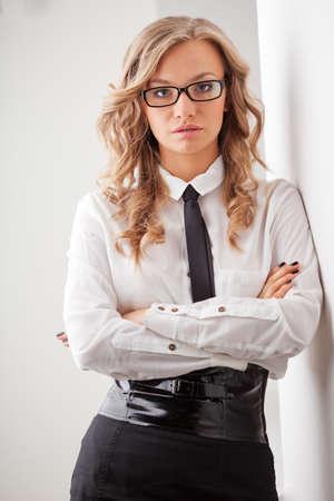closeup seriously blonde businesswoman portrait wearing eyeglasses standing near wall photo