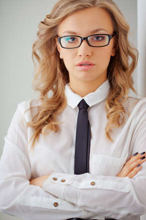 closeup seriously blonde businesswoman portrait wearing eyeglasses standing near wall photo