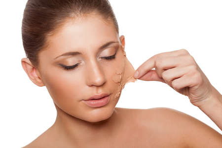 rejuvenate: beautiful woman taking of her old dry skin from face