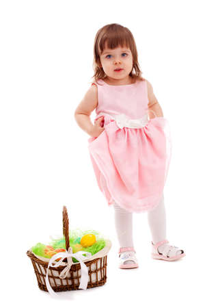 floor standing: little girl  standing near basket with eaters eggs over white Stock Photo
