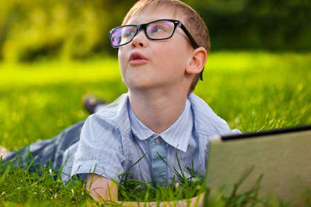 funny boy laying on green grass in the park with laptop photo