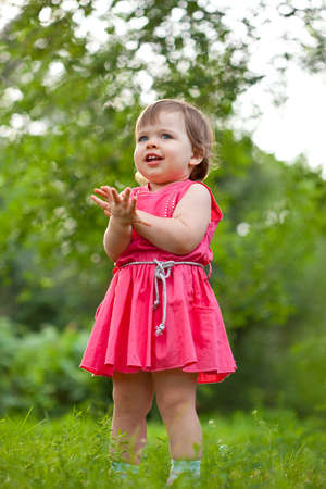 little girl in pink dress stading on meadow and clapping hands photo