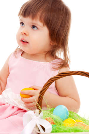 little girl playing with eater eggs near basket over white background photo