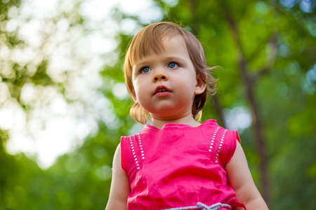 cute little girl in pink dress stading in park, low point of view photo