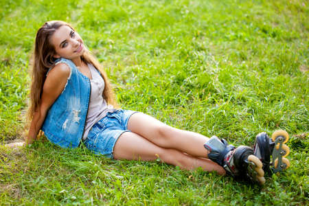 rollerblade: girl wearing roller skates sitting on grass in the park, top point of view
