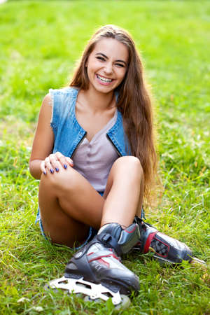rollerskating: laughing girl wearing roller skates sitting on grass in the park