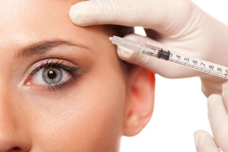 aesthetic: closeup beautiful woman eye, syringe injection beauty concept Stock Photo