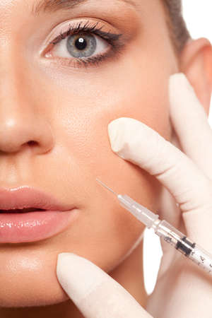 facelift: closeup beautiful woman face, syringe injection to nasolabial fold  beauty concept Stock Photo