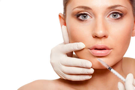 closeup beautiful woman face, syringe injection into lips, space for text photo