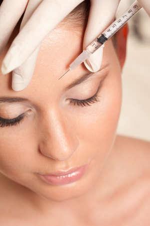 closeup schöne Frau Gesicht, Spritze Injektion Stirn, Beauty-Konzept Lizenzfreie Bilder