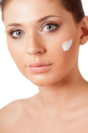 beautiful brunette woman face with cream on cheek over white Stock Photo - 18388212