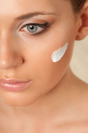 closeup beautiful woman face with cream on cheek over white photo