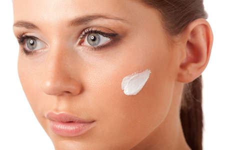 beautiful brunette  woman face with cream on cheek over white photo