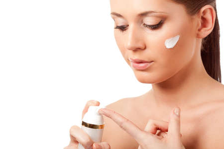 beautiful woman face with cream on cheek over white, she hold bottle in hands photo